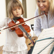 Young girl playing violin in music lesson - Stock Photo