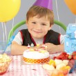 Young boy with birthday cake and gifts at party — Stock Photo