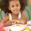 Young girl with birthday cake at party — Stock Photo #11890302