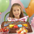 Young girl with birthday cake and gifts at party — Stock Photo
