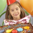 Young girl with birthday cake at party — Stock Photo
