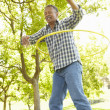 Senior  man with hula-hoop - Stock Photo