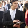Stock Photo: Male commuter in crowd with tablet and headphones