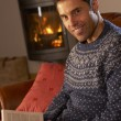 Middle Aged Man Relaxing With Book By Cosy Log Fire - Stock Photo
