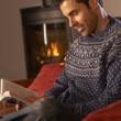 图库照片: Middle Aged MRelaxing With Book By Cosy Log Fire