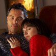 Middle Aged Couple Cuddling On Sofa By Cosy Log Fire — Stock Photo