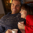 Middle Aged Couple Sitting On Sofa By Cosy Log Fire With Hot Dri — Stock Photo #11890565