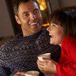 Middle Aged Couple Sitting On Sofa By Cosy Log Fire With Hot Dri - Stock Photo