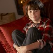 Young Boy Sitting On Sofa By Cosy Log Fire — Stock Photo #11890575