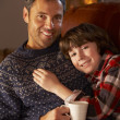 Stock Photo: Father And Son Relaxing With Hot Drink Watching TV By Cosy Log F
