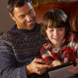 Foto Stock: Father And Son Using Tablet Computer By Cosy Log Fire