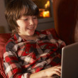Young Boy Relaxing With Laptop By Cosy Log Fire — Stock Photo #11890632
