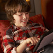Foto Stock: Young Boy Relaxing With Tablet Computer By Cosy Log Fire