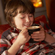 Young Boy Relaxing With Hot Drink By Cosy Log Fire — Stock Photo