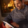 Middle Aged MUsing Tablet Computer By Cosy Log Fire — Stockfoto #11890687