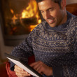 Middle Aged MUsing Tablet Computer By Cosy Log Fire — Stock Photo #11890687