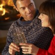 Middle Aged Couple Sitting Sofa By Cosy Log Fire With Glass Of C — Stock Photo #11890707