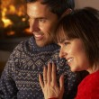Foto Stock: Middle Aged Couple Sitting SofWatching TV By Cosy Log Fire