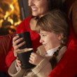 Mother And Daughter Relaxing With Hot Drink Watching TV By Cosy — Stock Photo #11890803