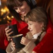Mother And Daughter Relaxing With Hot Drink Watching TV By Cosy — Stock Photo #11890806