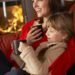 Mother And Daughter Relaxing With Hot Drink Watching TV By Cosy — Stock Photo #11890813