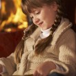 Young Girl Sitting On Sofa And Reading Book By Cosy Log Fire — Stock Photo