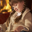 Young Girl Sitting On Sofa And Reading Book By Cosy Log Fire — Stock Photo #11890836