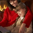 Mother And Daughter Sitting On Sofa And Reading Book By Cosy Log — Stock Photo #11890847