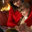 Mother And Daughter Sitting On Sofa And Reading Book By Cosy Log — Stock Photo #11890850