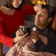 Wife Nursing Sick Husband With Cold Resting On Sofa By Cosy Log — Stock Photo