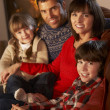 Portrait Of Family Relaxing On Sofa By Cosy Log Fire — Stock Photo