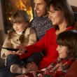 Foto Stock: Family Relaxing Watching TV By Cosy Log Fire