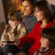 Family Relaxing Watching TV By Cosy Log Fire — Foto Stock