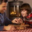 Father And Son Playing Chess By Cosy Log Fire — Stockfoto #11890933