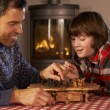 图库照片: Father And Son Playing Chess By Cosy Log Fire