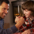 Father And Son Arm Wrestling By Cosy Log Fire - Stock Photo