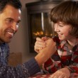 Father And Son Arm Wrestling By Cosy Log Fire — Stock Photo