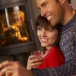 Stock Photo: Middle Aged Couple Sitting On Sofa Watching TV By Cosy Log Fire