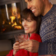 Middle Aged Couple Sitting On Sofa Watching TV By Cosy Log Fire - Stock fotografie