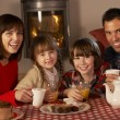 Foto Stock: Portrait Of Family Enjoying TeAnd Cake By Cosy Log Fire
