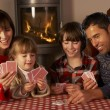 Portrait Of Family Playing Cards By Cosy Log Fire — Stock Photo #11890990