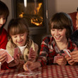 Foto Stock: Portrait Of Family Playing Cards By Cosy Log Fire