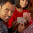 Stock Photo: Couple Playing Cards By Cosy Log Fire