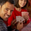 Stockfoto: Couple Playing Cards By Cosy Log Fire