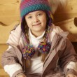 Young Girl Sitting On Wooden Seat Wearing Warm Outdoor Clothes - 图库照片