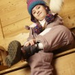 Young Girl Sitting On Wooden Seat Putting On Warm Outdoor Clothe - Stockfoto