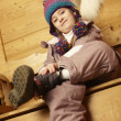 Young Girl Sitting On Wooden Seat Putting On Warm Outdoor Clothe - Stock Photo