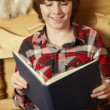 Stock Photo: Young Boy Sitting On Wooden Seat Reading Book