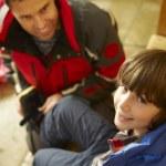 pai ajudando o filho para colocar nas botas e roupas quentes ao ar livre — Foto Stock