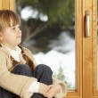 Young Girl Sitting On Window Ledge Looking At Snowy View — Stock Photo